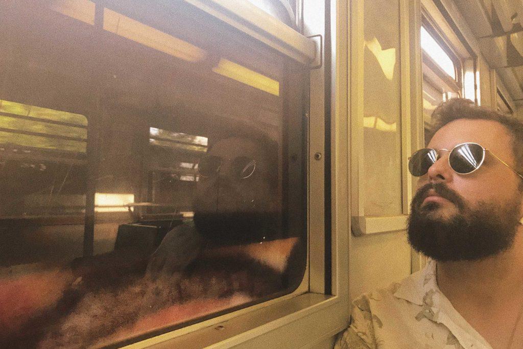 homem olhando pela janela de trem