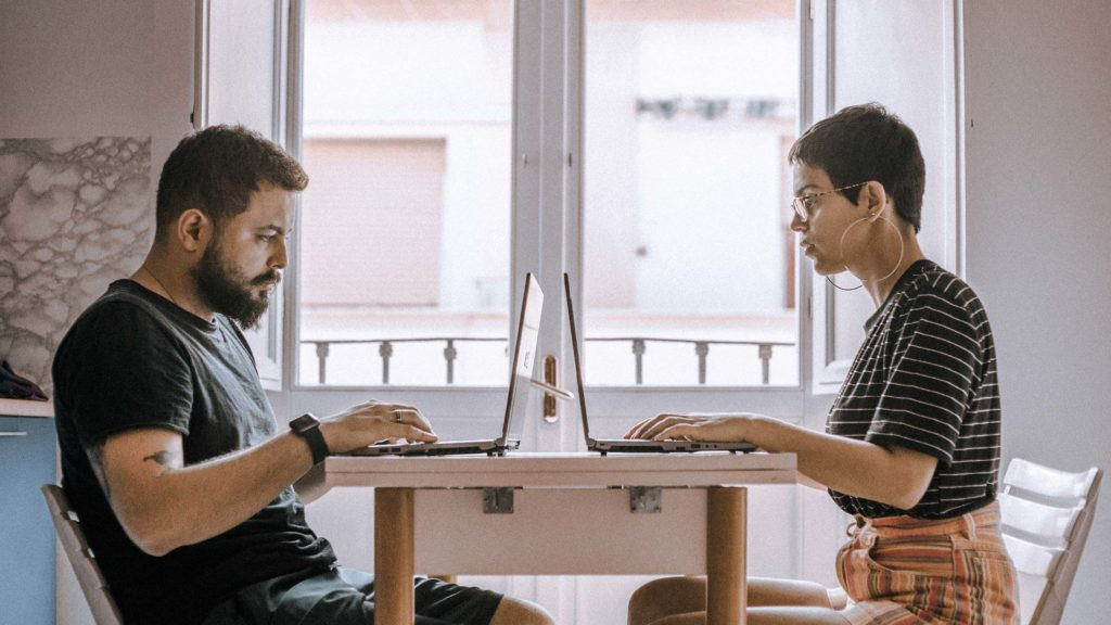 casal trabalhando nos seus notebooks em mesa na sala